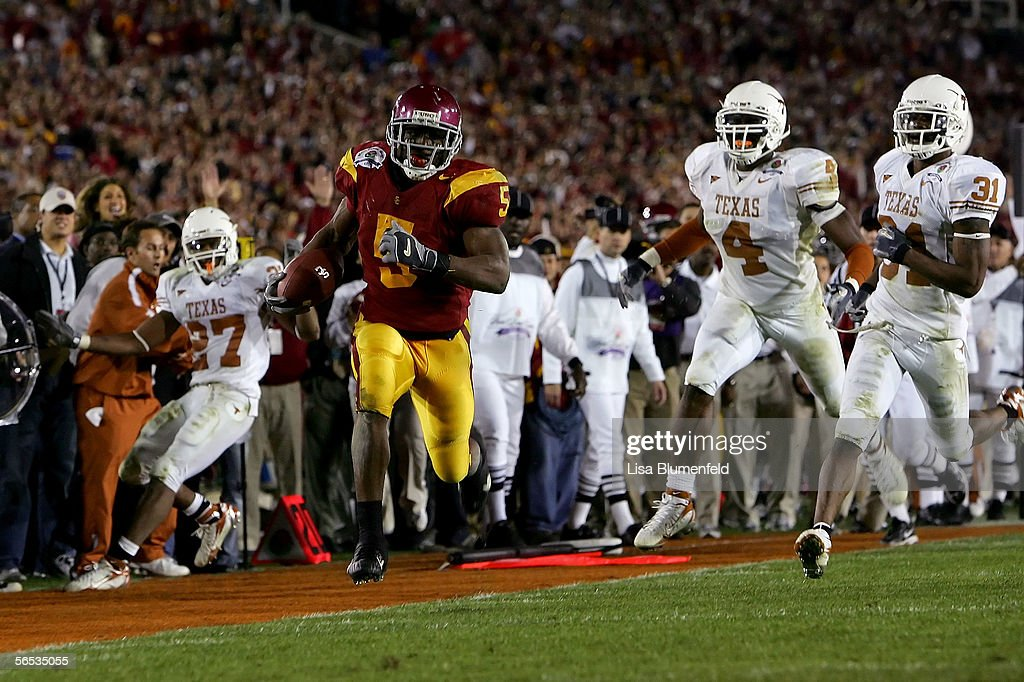 Reggie Bush #5 of the USC Trojans runs past Michael Griffin #27, Drew Kelson #4 and Aaron Ross #31 of the Texas Longhorns en route to scoring a 26 yeard touchdown in the fourth quarter of the BCS National Championship Rose Bowl Game at the Rose Bowl on January 4, 2006 in Pasadena, California. Texas defeated USC
