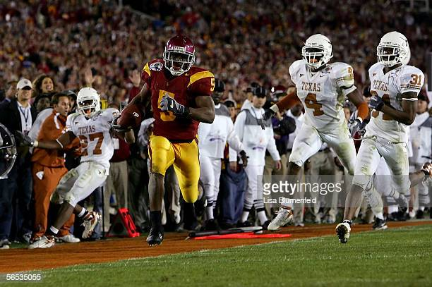 Reggie Bush of the USC Trojans runs past Michael Griffin Drew Kelson and Aaron Ross of the Texas Longhorns en route to scoring a 26 yeard touchdown...