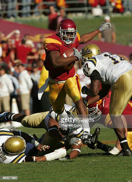 Reggie Bush of the USC Trojans rushes the ball past the UCLA Bruins defense December 3, 2005 at the Los Angeles Memorial Coliseum in Los Angeles,...