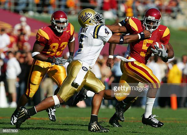 Reggie Bush of the USC Trojans stiffarms Jarrad Page the UCLA Bruins as he runs with the ball December 3 2005 at the Los Angeles Memorial Coliseum in...