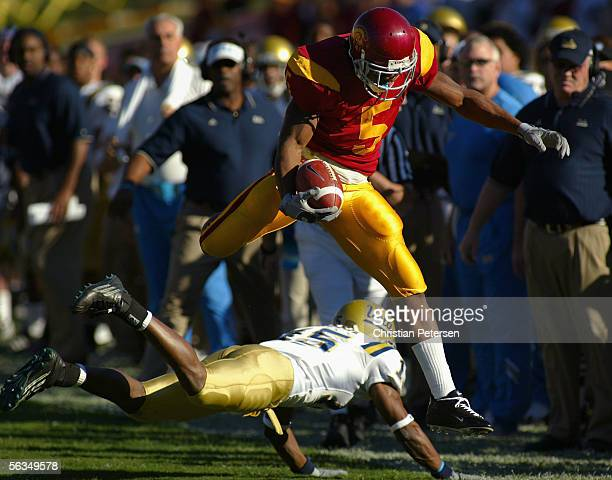 Reggie Bush of USC Trojans leaps over Marcus Cassel of the UCLA Bruins during the game on December 3, 2005 at the Los Angeles Memorial Coliseum in...
