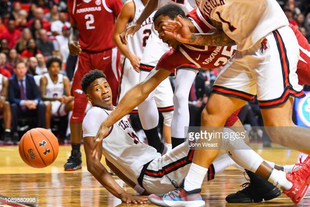 Reggie Chaney of the Arkansas Razorbacks loses the ball out of bounds as Jarrett Culver of the Texas Tech Red Raiders looks on during the first half...