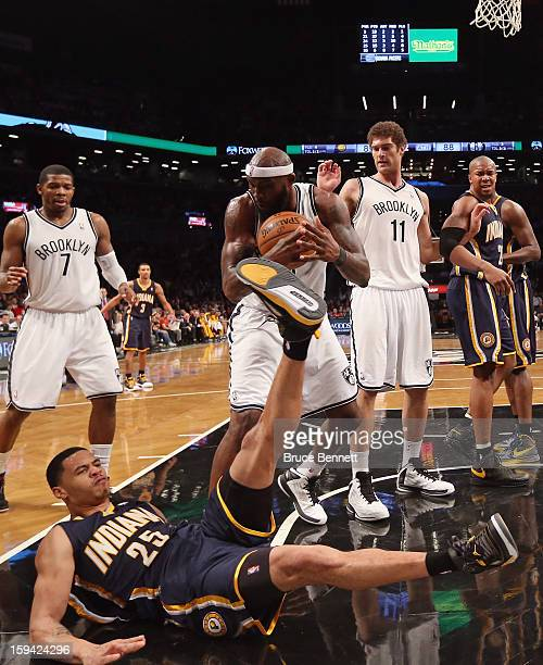 Reggie Evans of the Brooklyn Nets and Gerald Green of the Indiana Pacers battle over a loose ball in the fourth quarter at the Barclays Center on...