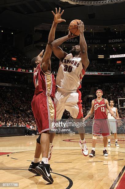 Reggie Evans of the Toronto Raptors shoots against Leon Powe of the Cleveland Cavaliers during the game on February 26 2010 at Air Canada Centre in...