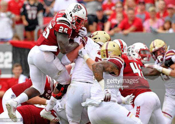 Reggie Gallaspy II of the North Carolina State Wolfpack crashes into the pile during their game against the Boston College Eagles at Carter-Finley...