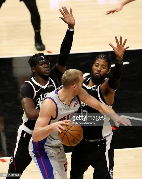 Reggie Jackson and Paul George of the Los Angeles Clippers pressure Mason Plumlee of the Detroit Pistons during the third quarter at Staples Center...
