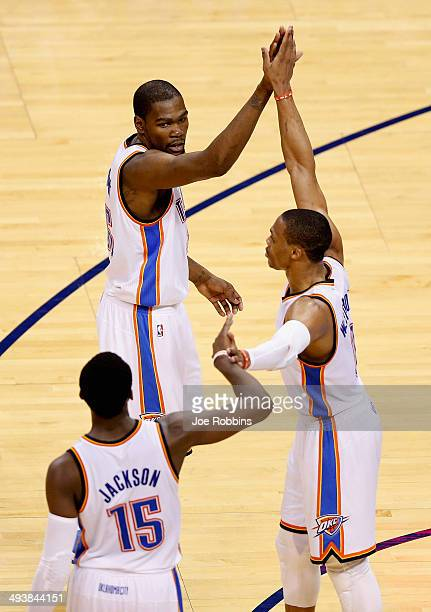 Reggie Jackson Kevin Durant and Russell Westbrook of the Oklahoma City Thunder high five in the third quarter against the San Antonio Spurs during...