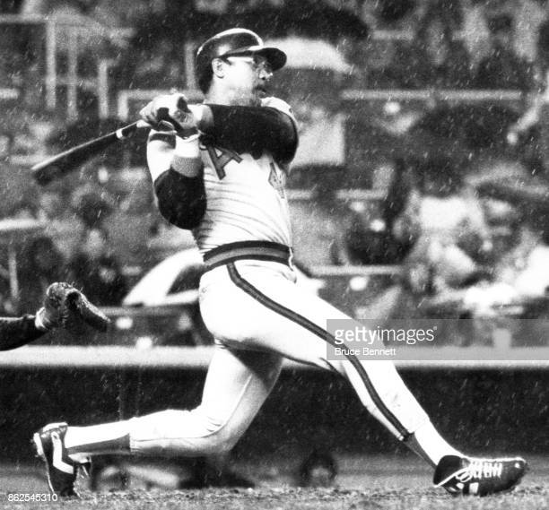 Reggie Jackson of the California Angels hits a homerun as rain falls during an MLB game against the New York Yankees on April 27 1982 at Yankee...