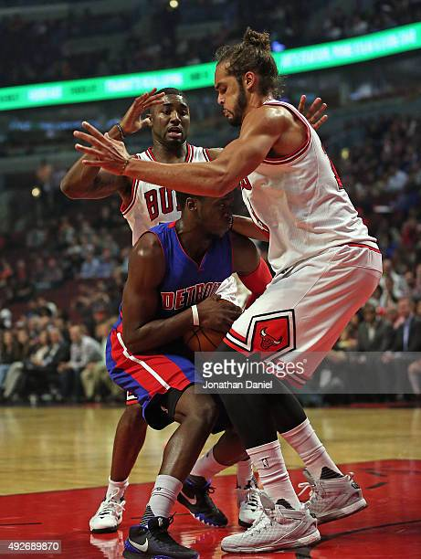 Reggie Jackson of the Detroit Pistons is trapped by Joakim Noah and E'Twaun Moore of the Chicago Bulls during a preseason game at the United Center...