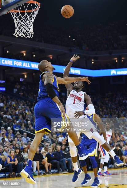Reggie Jackson of the Detroit Pistons shoots over David West of the Golden State Warriors during an NBA basketball game at ORACLE Arena on October 29...