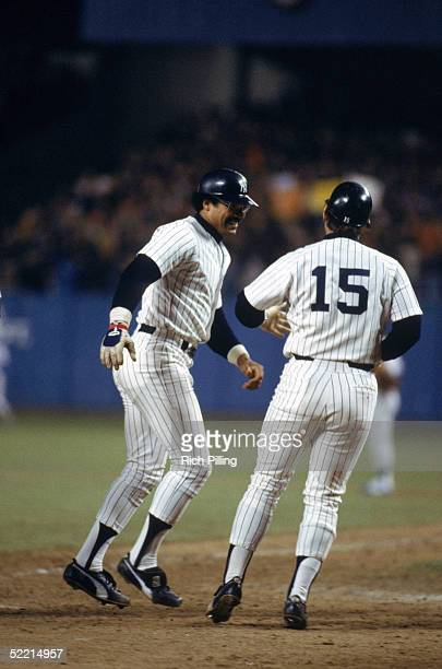 Reggie Jackson of the New York Yankees celebrates with Thurman Munson after hitting his third home run during the 1977 World Series game 6 against...