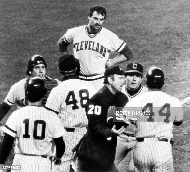 Reggie Jackson of the New York Yankees is being held back by umpire Dale Ford and Mike Hargrove of the Cleveland Indians after being knocked down by...