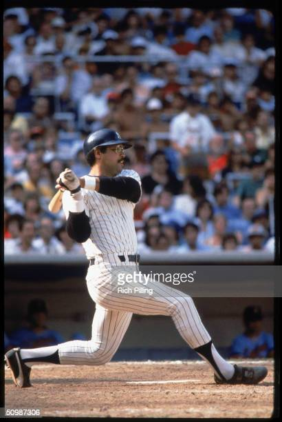 Reggie Jackson of the New York Yankees watches the flight of the ball as he follows through on a swing during a game in 1978 at Yankee Stadium in...