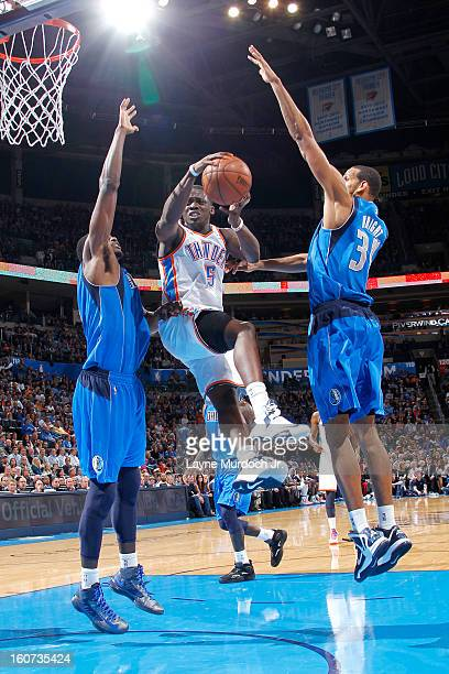 Reggie Jackson of the Oklahoma City Thunder goes to the basket against Bernard James and Brandan Wright of the Dallas Mavericks of the Dallas...