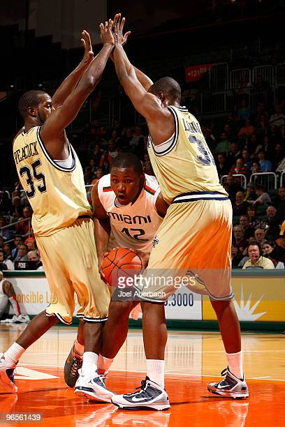 Reggie Johnson of the Miami Hurricanes dribbles the ball between Zachery Peacock and Gani Lawal of the Georgia Tech Yellow Jackets on February 10...
