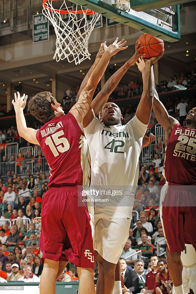 Reggie Johnson #42 of the Miami Hurricanes goes to the basket between Aaron Thomas #25 and Boris Bojanovsky #15 of the Florida State Seminoles on January 27, 2013 at the BankUnited Center in Coral Gables, Florida. The Hurricanes defeated the Seminoles 71-47.