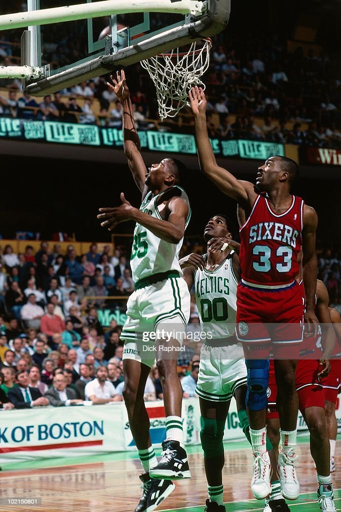 Reggie Lewis #35 of the Boston Celtics shoots against Hersey Hawkins #33 of the Philadelphia 76ers during a game played in 1990 at the Boston Garden in Boston, Massachusetts.