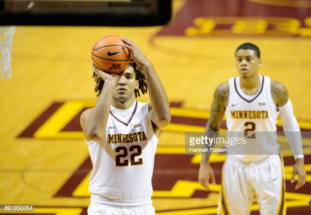 Reggie Lynch of the Minnesota Golden Gophers shoots a free throw against the Drake Bulldogs as teammate Nate Mason looks on during the game on...