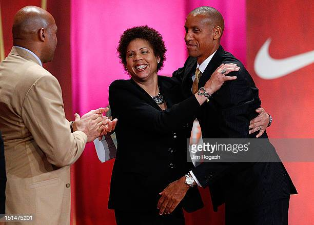 Reggie Miller is hugged by his sister Cheryl Miller as Charles Barkley applauds during the Basketball Hall of Fame Enshrinement Ceremony at Symphony...