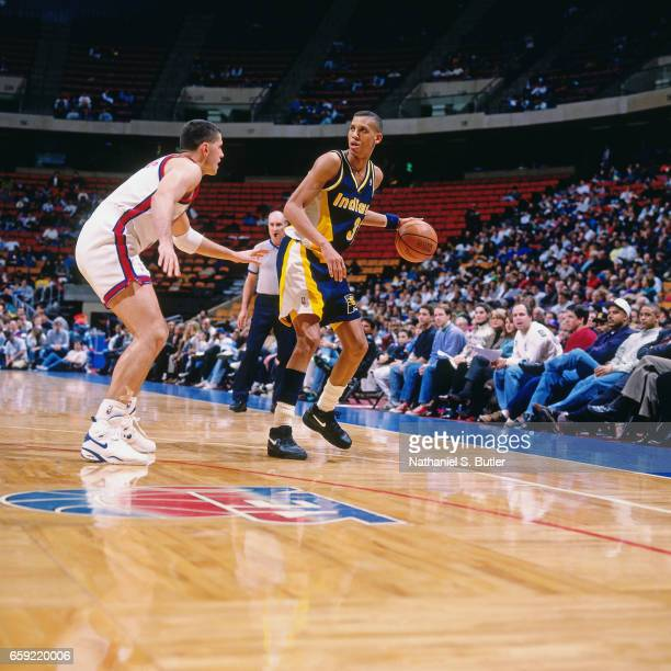 Reggie Miller of the Indiana Pacers dribbles against Drazen Petrovic of the New Jersey Nets during a game played circa 1993 at the Brendan Byrne...