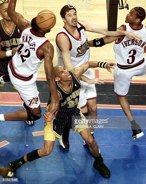 Reggie Miller of the Indiana Pacers is surrounded by Allen Iverson Tony Kukoc and Theo Ratliff of the Philadelphia 76ers during the 1st quarter of...