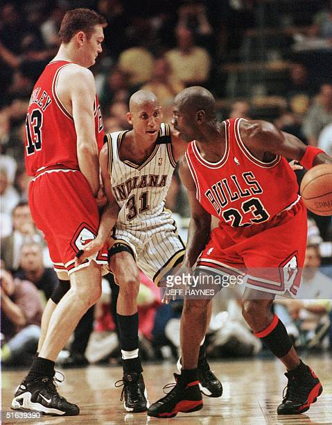 Reggie Miller of the Indiana Pacers runs into a pick set by Luc Longley of the Chicago Bulls for teammate Michael Jordan 29 May during the first half...