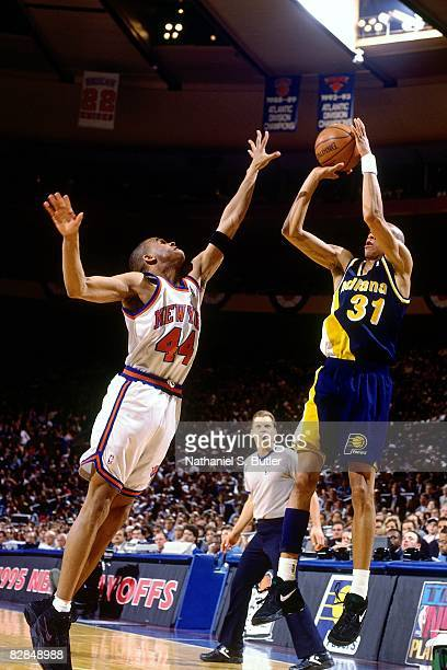 Reggie Miller of the Indiana Pacers shoots against Hubert Davis of the New York Knicks in Game Two of the 1995 Eastern Conference Semifinals played...