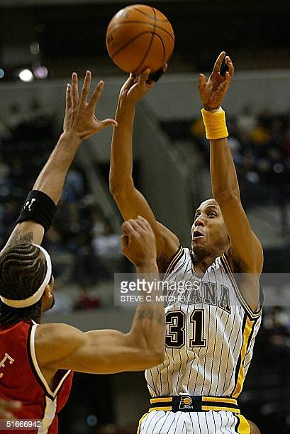 Reggie Miller of the Indiana Pacers shoots over Ira Newbie of the Atlanta Hawks in the second half 23 December 2002 at Conseco Fieldhouse in...