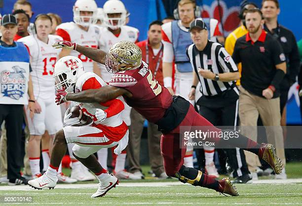 Reggie Northrup of the Florida State Seminoles tackles Demarcus Ayers of the Houston Cougars in the first quarter during the ChickfilA Peach Bowl at...