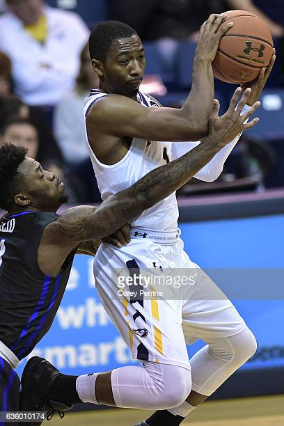 Reggie Reid of the Florida Gulf Coast Eagles reaches in on Johnnie Shuler of the La Salle Explorers during the first half at Tom Gola Arena on...