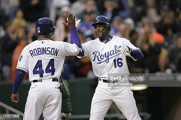Reggie Sanders of the Kansas City Royals is congratulated by Kerry Robinson after hitting a 1stinning grand slam during action between the Oakland...