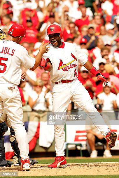 Reggie Sanders of the St. Louis Cardinals celebrates at home plate with teammate Albert Pujols after Sanders hit a grand slam in the fifth inning...