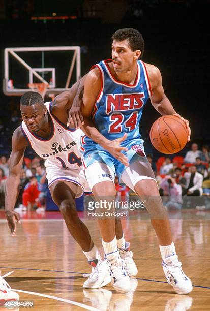 Reggie Theus of the New Jersey Nets drives past AJ English of the Washington Bullets during an NBA basketball game circa 1991 at the Capital Centre...