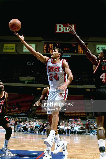 Reggie Theus of the New Jersey Nets drives to the basket for a layup against the Miami Heat during a NBA game in 1991 at the Brendan Byrne Arena in...