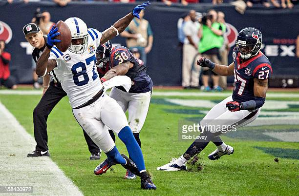 Reggie Wayne of the Indianapolis Colts completes a pass in the endzone as he beats Danieal Manning and Quintin Demps of the Houston Texans on the...