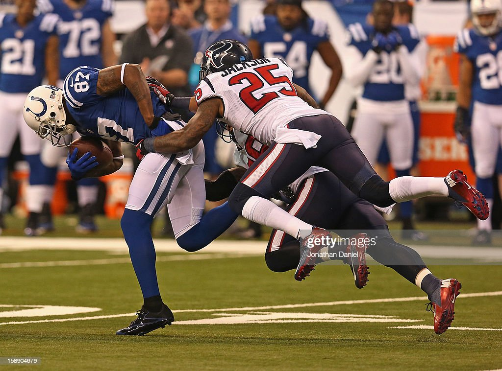 Reggie Wayne #87 of the Indianapolis Colts tries to break away from Kareem Jackson #25 and Glover Quin #29 of the Houston Texans at Lucas Oil Stadium on December 30, 2012 in Indianapolis, Indiana. The Colts defeated the Texans 28-16.