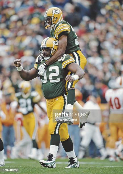 Reggie White Defensive End for the Green Bay Packers gives a piggyback to team mate Doug Evans during the National Football Conference Central game...