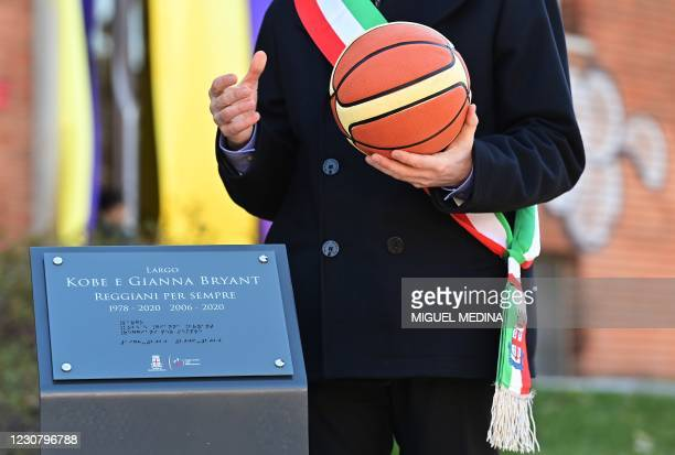 Reggio Emilia mayor Luca Vecchi holds a basket ball near the commemorative plaque during the inauguration ceremony of a square named after late Los...