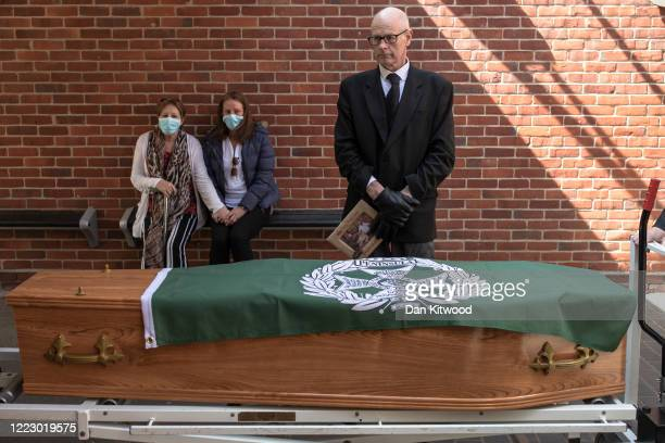 A regimental flag is placed on the coffin of Eric Stonestreet while family and friends watch from a distance ahead of his funeral service at Ipswich...