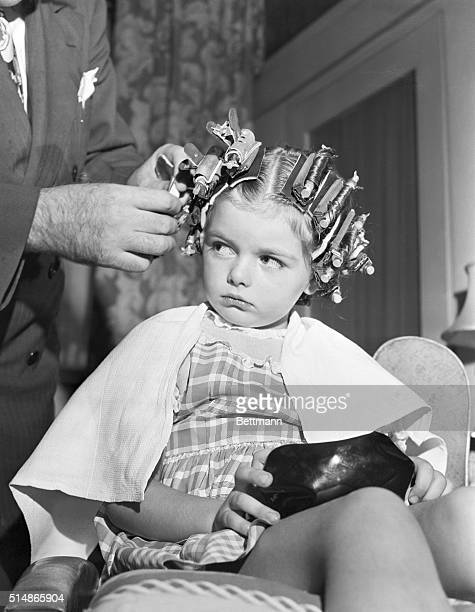 Regina a little girl glances irritably at John Hall as he styles her hair for permanent waves