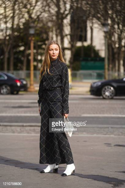 Regina Anikiy wears a black checked jacket, flared pants, a white bag, white and black pointy boots, outside Chanel, during Paris Fashion Week -...