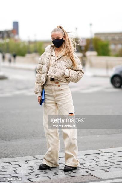 Regina Anikiy wears a Vuitton black protective face mask, a beige Vuitton monogram printed puffer coat, a jacket, Vuitton white flared pants, brown...