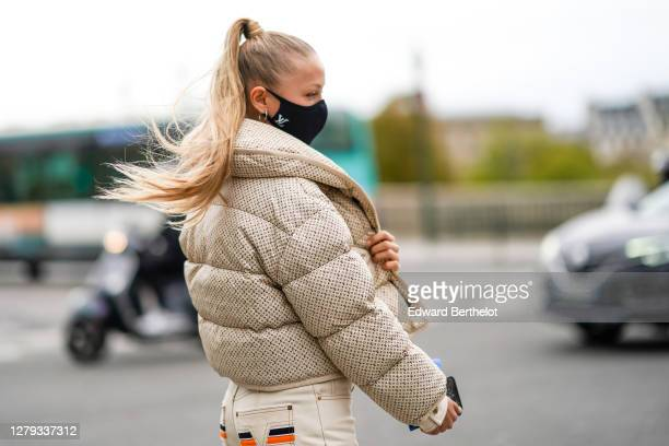 Regina Anikiy wears a Vuitton black protective face mask, a beige Vuitton monogram printed puffer coat, a jacket, outside Louis Vuitton, during Paris...