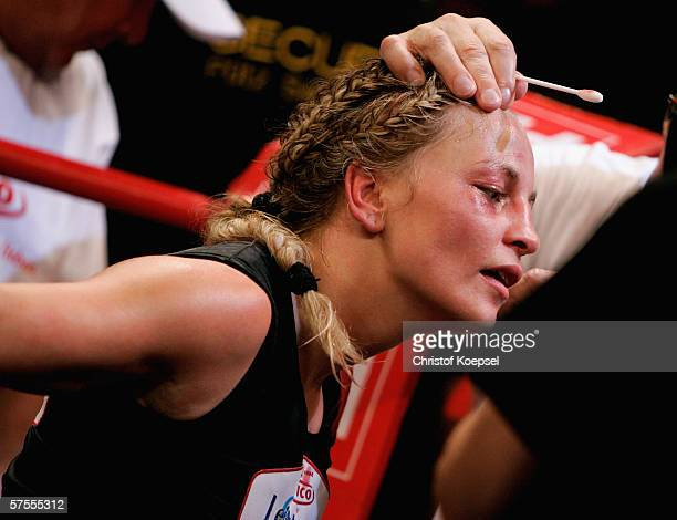 Regina Halmich is treated by a doctor because of an injury to her eye during the WIBF Women flyweight world championship fight between Regina Halmich...