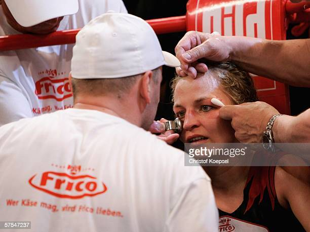 Regina Halmich is treated by a doctor for an injury on the eyebrow during the WIBF Women flyweight world championship fight between Regina Halmich of...