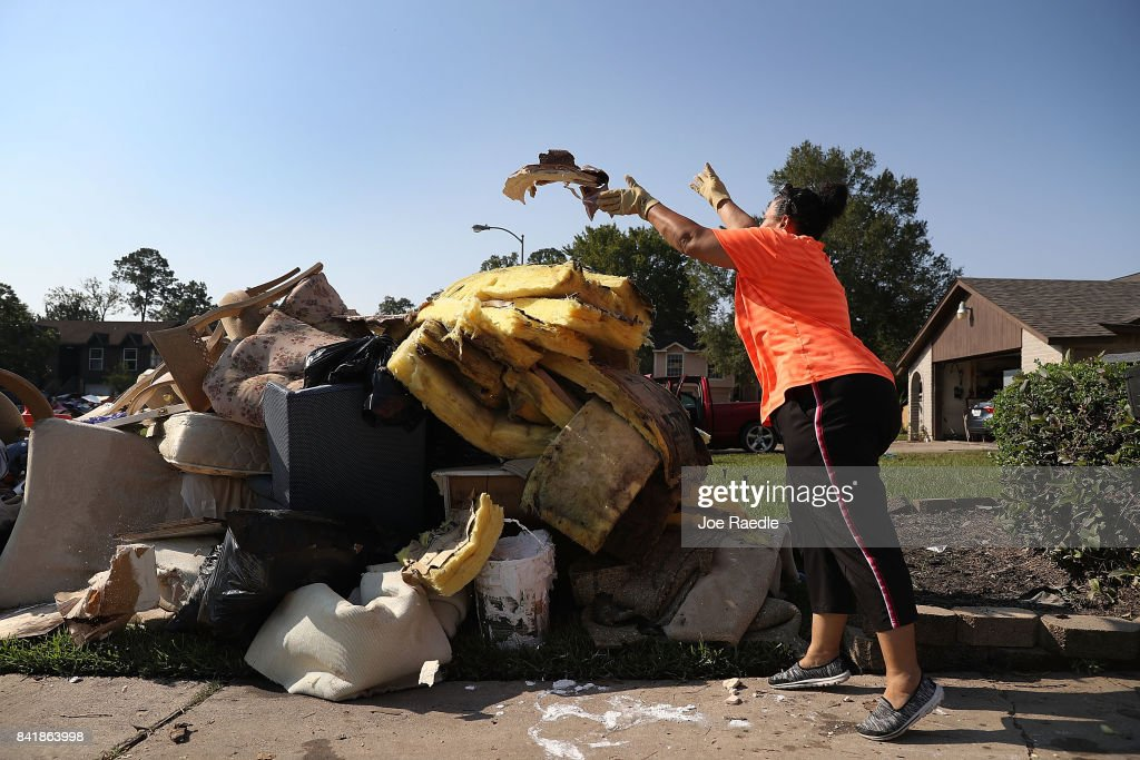 Regina Perry throws out wet sheetrock as she cleans out of her home that was inundated with water as she begins the process of rebuilding after torrential rains caused widespread flooding during Hurricane and Tropical Storm Harvey on September 2, 2017 in Houston, Texas. Harvey, which made landfall north of Corpus Christi on August 25, dumped around 50 inches of rain in and around areas of Houston and Southeast Texas.