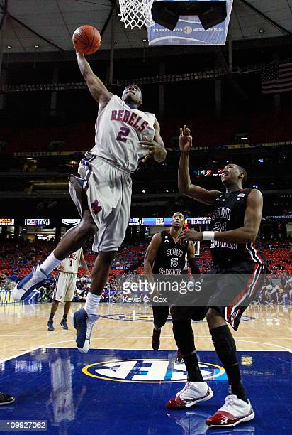Reginald Buckner of the Ole Miss Rebels shoots over Damontre Harris of the South Carolina Gamecocks during the first round of the SEC Men's...