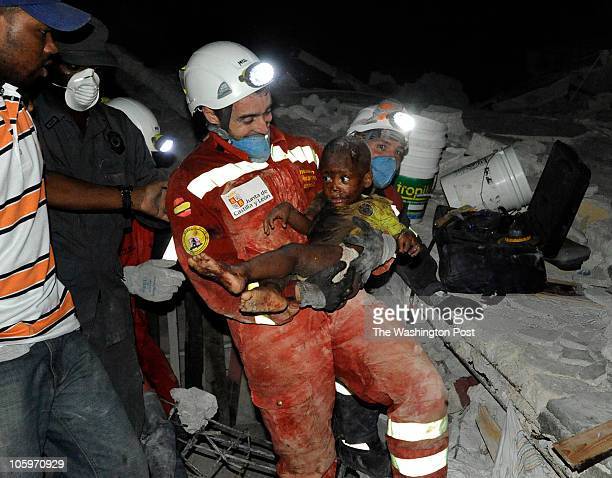 Reginald Claude looks on as his young son Reggie Claude is carried by Oscar Vega Carrera from Groupo Rescate Emergencias from Castilla Y Leon Reggie...