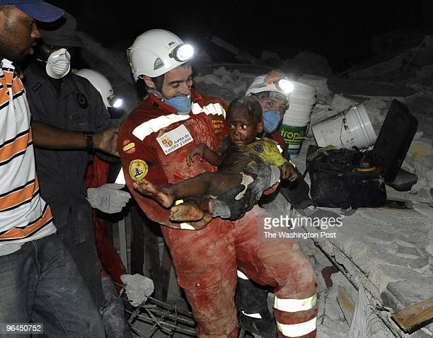 Reginald Claude looks on as his young son Reggie Claude is carried by Oscar Vega Carrera from Groupo Rescate Emergencias from Castilla Y Leon on...