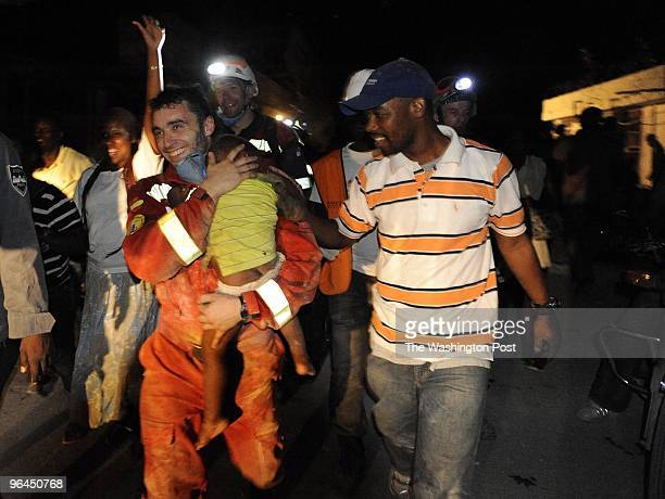 Reginald Claude walks beside Oscar Vega Carrera from Groupo Rescate Emergencias from Castilla Y Leon who is carrying Claude's young son Reggie Claude...